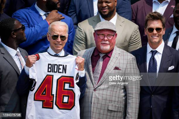 President Joe Biden holds up a Buccaneers jersey while standing next to head coach Bruce Arians and quarterback Tom Brady as he welcomes the 2021 NFL...