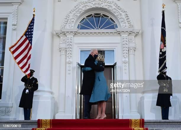 President Joe Biden hugs First Lady Jill Biden as they arrive at the White House in Washington, DC, on January 20, 2021.