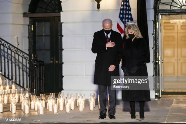 President Joe Biden, left, and First Lady Jill Biden hold a moment of silence and candle lighting during a ceremony to honor lives lost to Covid-19...