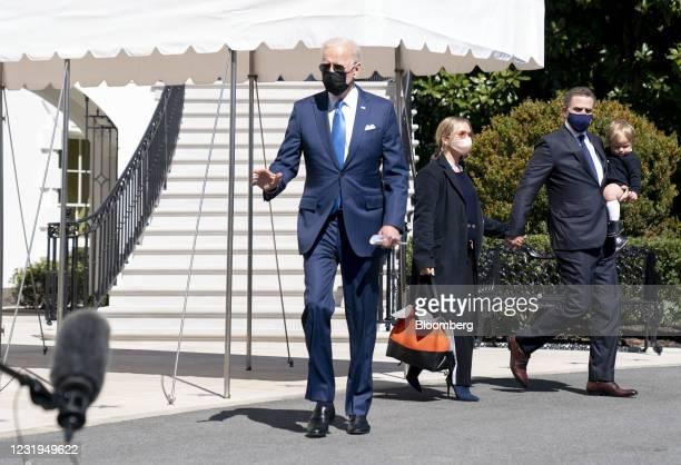 President Joe Biden, left, walks beside his son Hunter Biden, Melissa Cohen Biden and their son on the South Lawn of the White House before boarding...