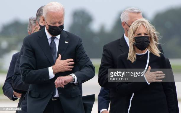 President Joe Biden looks down alongside First Lady Jill Biden as they attend the dignified transfer of the remains of a fallen service member at...