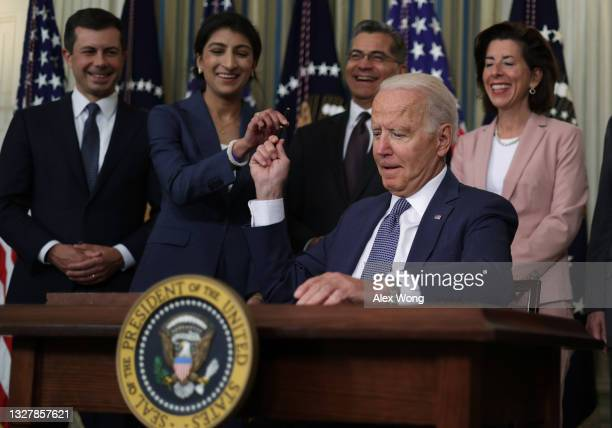 President Joe Biden passes a signing pen to Chairperson of the Federal Trade Commission Lina Khan as Secretary of Transportation Pete Buttigieg,...