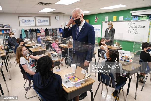President Joe Biden points to his hair after a student told him she wanted to be a hairstylist when she grows up, as he and First Lady Jill Biden...