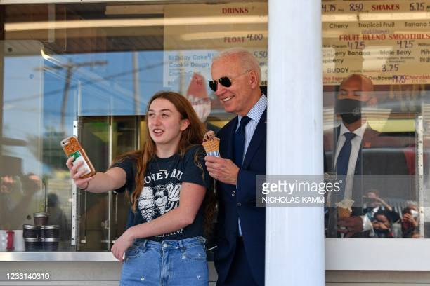 President Joe Biden poses for a photo with a girl after getting an ice cream at Honey Hut Ice Cream in Cleveland, Ohio, on May 27, 2021.