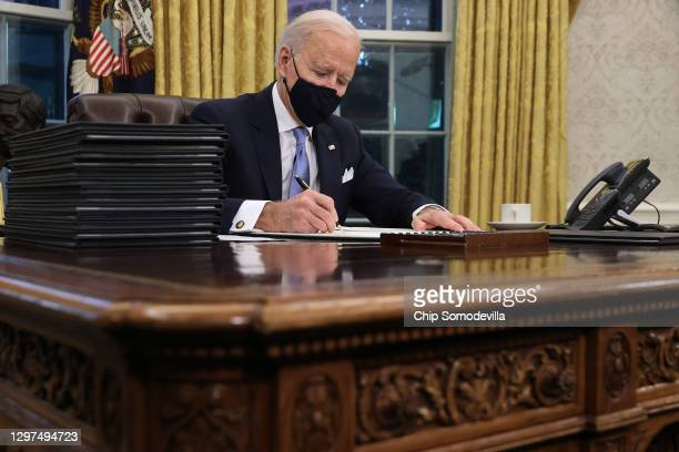 President Joe Biden prepares to sign a series of executive orders at the Resolute Desk in the Oval Office just hours after his inauguration on...