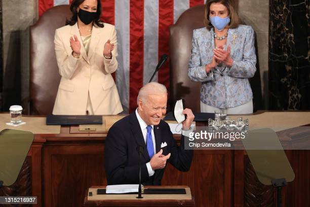 President Joe Biden removes his face mask before addressing a joint session of Congress as Vice President Kamala Harris and Speaker of the House U.S....