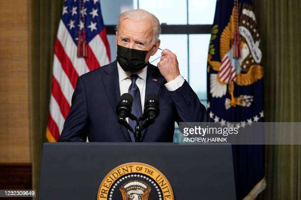 President Joe Biden removes his facemask before speaking from the Treaty Room in the White House on April 14, 2021 in Washington, DC, about the...