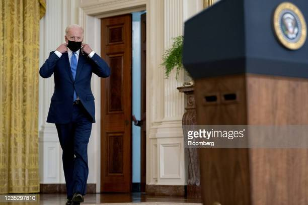 President Joe Biden removes his protective mask while arriving to speak in the East Room of the White House in Washington, D.C., U.S., on Thursday,...