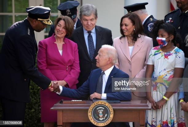President Joe Biden shakes hands with Chief Robert Contee III, of the DC Metropolitan Police Department, after signing legislation to award...