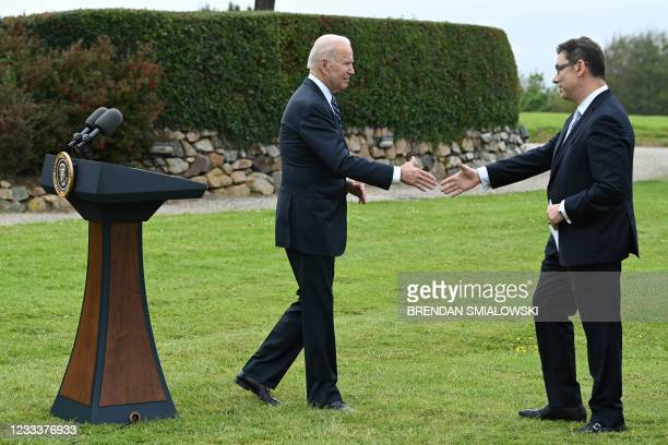 President Joe Biden shakes hands with Pfizer CEO Albert Bourla as he hands the podium over to him to make a statement in St Ives, Cornwall on June 10...