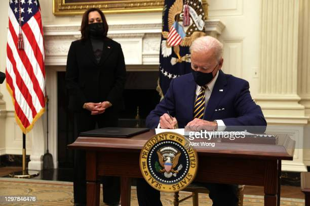 President Joe Biden signs an executive order as Vice President Kamala Harris looks on during an event on economic crisis in the State Dining Room of...