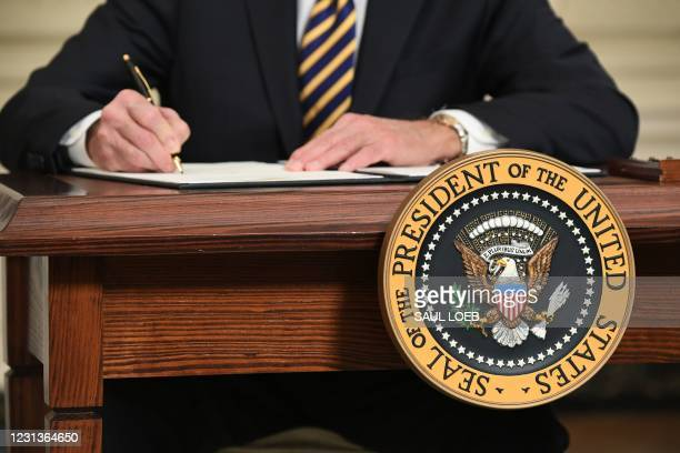 President Joe Biden signs an executive order on securing critical supply chains, in the State Dining Room of the White House in Washington, DC,...