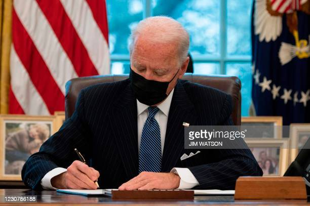 President Joe Biden signs an Executive Order reversing Trump era ban on Transgender serving in the military while in the Oval Office of the White...