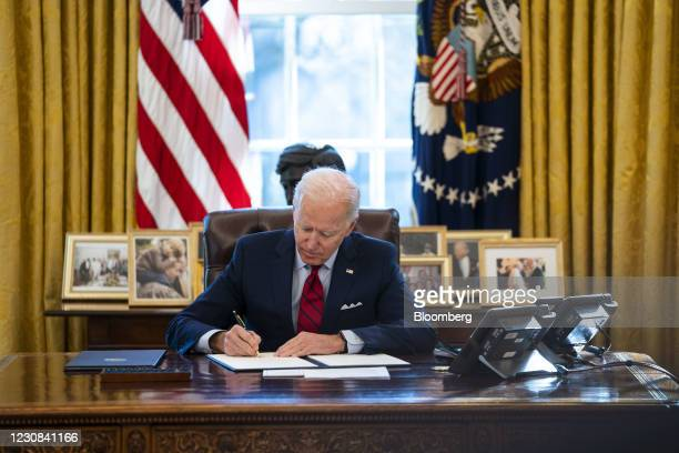 President Joe Biden signs executive actions in the Oval Office of the White House in Washington, D.C., U.S., on Thursday, Jan. 28, 2021. Biden will...