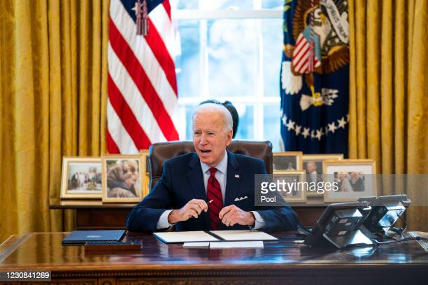 President Joe Biden signs executive actions in the Oval Office of the White House on January 28, 2021 in Washington, DC. President Biden signed a...