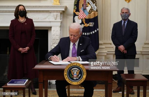 President Joe Biden signs executive orders as part of the Covid-19 response as US Vice President Kamala Harris and Director of NIAID Anthony Fauci...