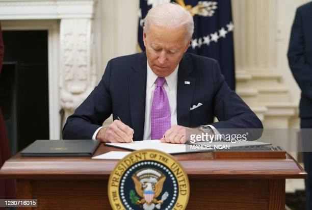 President Joe Biden signs executive orders as part of the Covid-19 response in the State Dining Room of the White House in Washington, DC, on January...