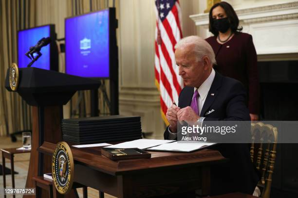 President Joe Biden signs executive orders as Vice President Kamala Harris looks on during an event at the State Dining Room of the White House...