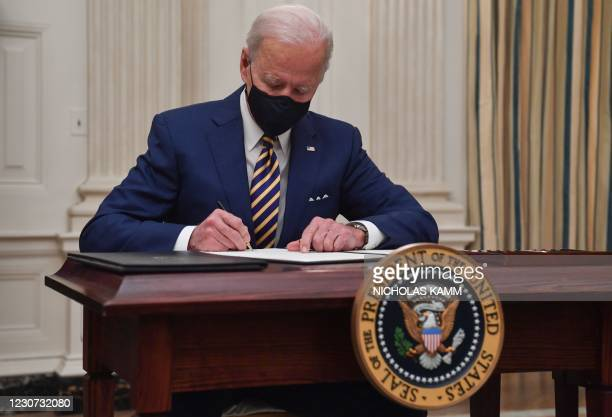 President Joe Biden signs executive orders for economic relief to Covid-hit families and businesses in the State Dining Room of the White House in...