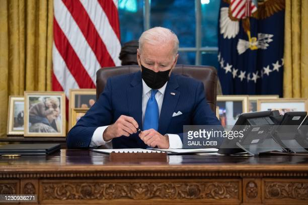 President Joe Biden signs executive orders related to immigration in the Oval Office of the White House in Washington, DC, February 2, 2021.