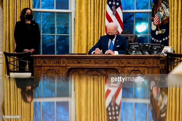 President Joe Biden signs several executive orders directing immigration actions for his administration as Vice President Kamala Harris looks on in...
