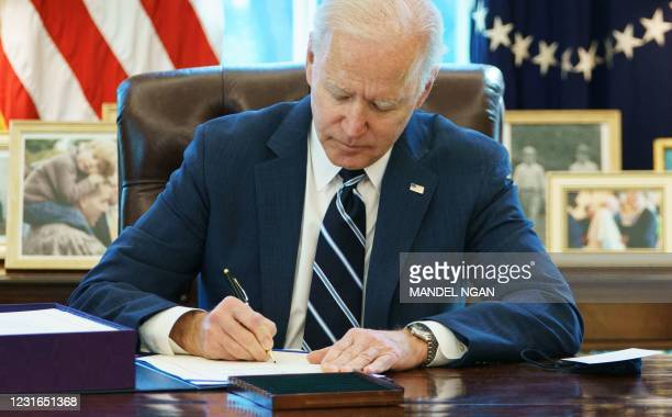 President Joe Biden signs the American Rescue Plan on March 11 in the Oval Office of the White House in Washington, DC. - Biden signed the $1.9...