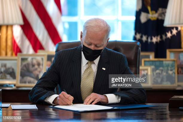 President Joe Biden signs the Paycheck Protection Program Extension Act of 2021 into law at the White House in Washington, DC, on March 30, 2021.