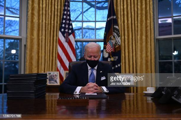 President Joe Biden sits in the Oval Office at the White House in Washington, DC, after being sworn in at the US Capitol on January 20, 2021. - US...
