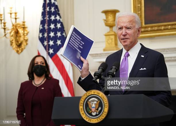 President Joe Biden speaks about the Covid-19 response as US Vice President Kamala Harris looks on before signing executive orders in the State...