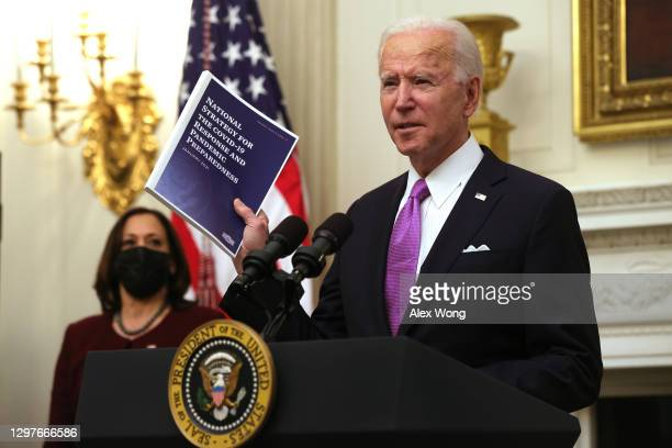 President Joe Biden speaks as Vice President Kamala Harris looks on during an event in the State Dining Room of the White House January 21, 2021 in...