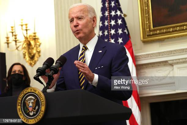 President Joe Biden speaks as Vice President Kamala Harris looks on during an event on economic crisis in the State Dining Room of the White House...