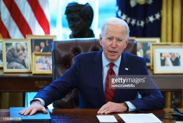 President Joe Biden speaks before signing executive orders on health care, in the Oval Office of the White House in Washington, DC, on January 28,...