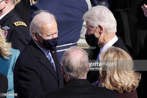 President Joe Biden speaks to former President Bill Clinton and former Secretary of State Hillary Clinton during his inauguration on the West Front...