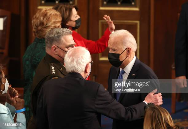 President Joe Biden speaks with Sen. Bernie Sanders after addressing a joint session of congress in the House chamber of the U.S. Capitol April 28,...