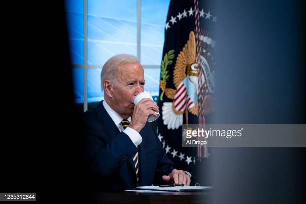 President Joe Biden takes a drink as he participates in a conference call on climate change with the Major Economies Forum on Energy and Climate in...