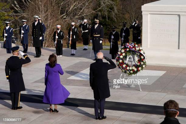 President Joe Biden , Vice President Kamala Harris, and Major General Omar J. Jones salute at the Tomb of the Unknown Soldier at the Arlington...