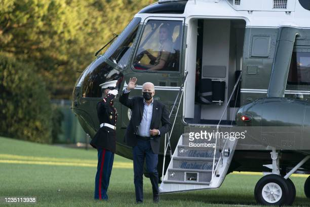 President Joe Biden waves to U.S. First Lady Jill Biden, not pictured, as he exits Marine One on the South Lawn of the White House in Washington,...