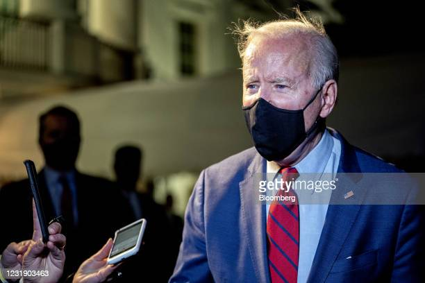 President Joe Biden wears a protective mask while speaking to members of the media on the South Lawn of the White House after arriving on Marine One...