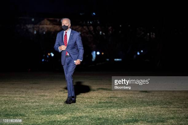President Joe Biden wears a protective mask while walking on the South Lawn of the White House after arriving on Marine One in Washington, D.C.,...
