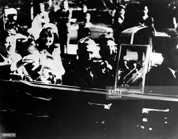 President John F Kennedy and his wife Jacqueline Kennedy ride with secret agents in an open car motorcade shortly before the president was...