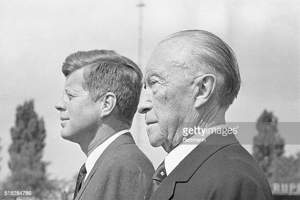 President John F. Kennedy and West German Chancellor Konrad Adenauer stand at attention following Kennedy's arrival at Wahn Airport.