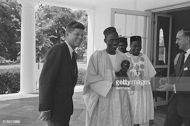 US President John F Kennedy escorts Nigerian Prime Minister Abubkar Tafawa Balewa from the White House Prime Minister Balewa carries a bust of...
