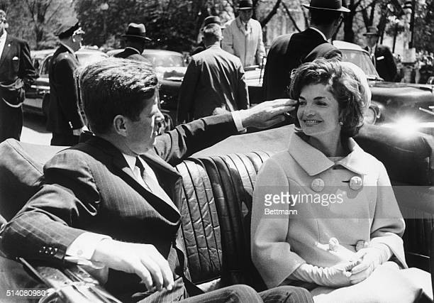 President John F Kennedy fixes Jacqueline's windblown hair as they ride in a convertible between Blair House and the White House They had just met...