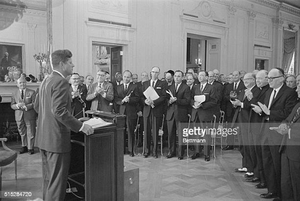 President John F. Kennedy is applauded as he arrives at the podium to address 250 religious leaders in the East Room of the White House today. The...