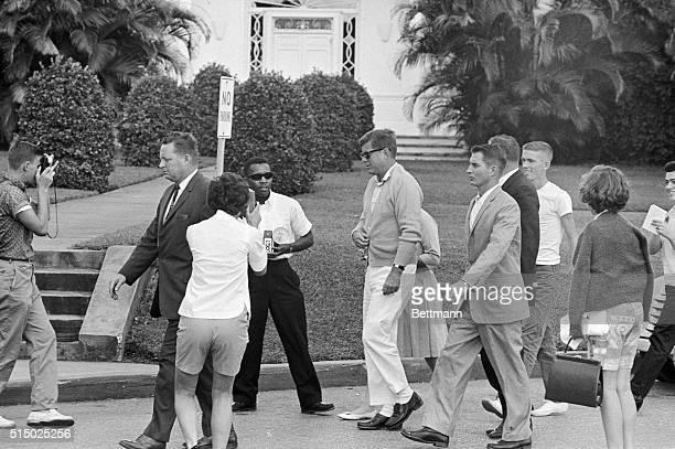 President John F Kennedy is surrounded by tourists as he walks with Secret Service agents from his automobile to St Mary' hospital