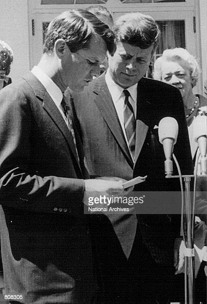 President John F Kennedy listens as his brother Robert speak at a White House ceremony May 7 1963