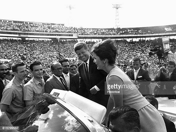 President John F Kennedy looks on as Jacqueline Kennedy speaks in Spanish to the soldiers of the Bay of Pigs Brigade from an open car Miami Florida...