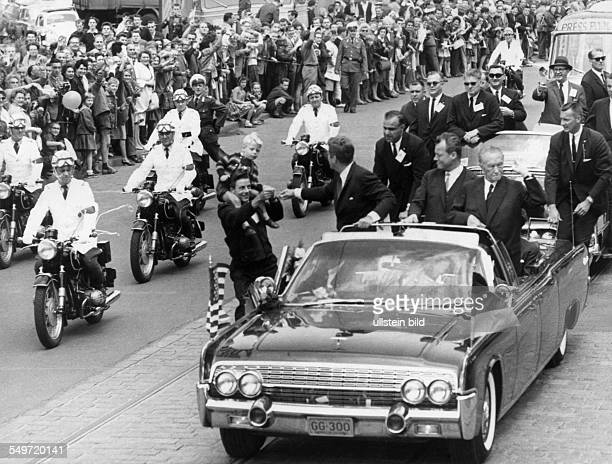 US President John F Kennedy on a visit to West Berlin ride in an open car through the city Kennedy turning to a man with a boy on his shoulders...