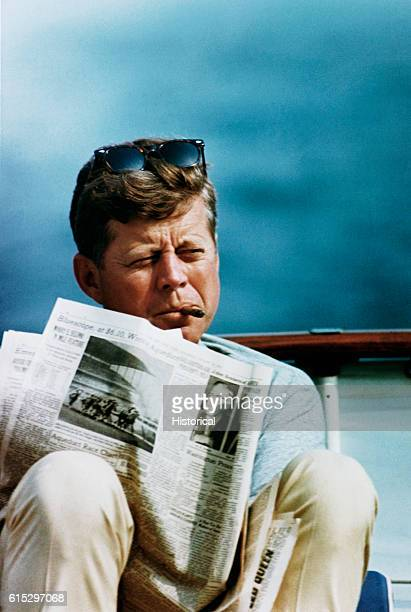 President John F Kennedy relaxes with a cigar and a newspaper aboard his family yacht the Honey Fitz Sailing was one of Kennedy's favorite pastimes