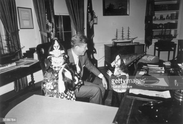 President John F Kennedy sits behind his desk laughing as his children Caroline and John Jr show him their Halloween costumes in the Oval Office of...
